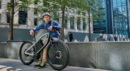 man met e-bike voor kantoor